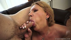 Horny granny masturbates on the couch until a cock walks up to suck