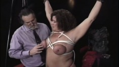 Chunky mature brunette takes some torture on her tits and ass in the dungeon