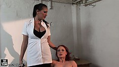 Petite redheaded slave in bondage gets teased by a busty brunette