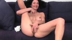 Seductive brunette milf Emanuelle sits on the couch and masturbates