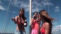 Three frisky young girls enjoy playing with their naked bodies on a yacht