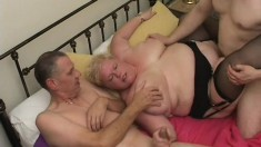 Mature chubby lady JJ lies on a bed as two thick cocks pound her holes