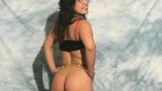 Fit brunette in black lingerie smiles as she poses on camera