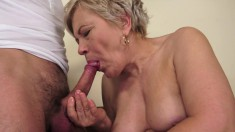 Busty old gal gets a young stud to fuck her mouth and shaved snatch