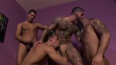 Tattooed gay stud has three lustful boys sharing his cock and his ass