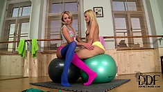 Taking a break from their yoga class, two sexy slender blondes have a little fun